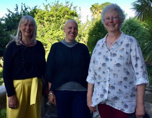 Three women standing together & smiling in a sunny garden