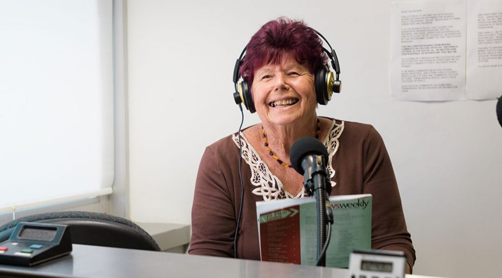 Radio 4RPH volunteer wearing headphones and holding a magazine, smiles as she reads into the studio mic.