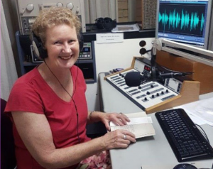 Volunteer Lesma Wood smiles as she reads from an open book into the studio mic