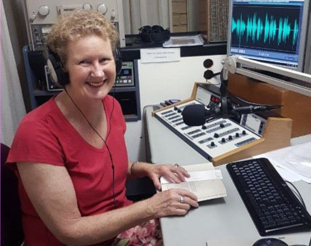 1RPH volunteer Lesma Wood smiles as she reads from an open book into the studio mic.