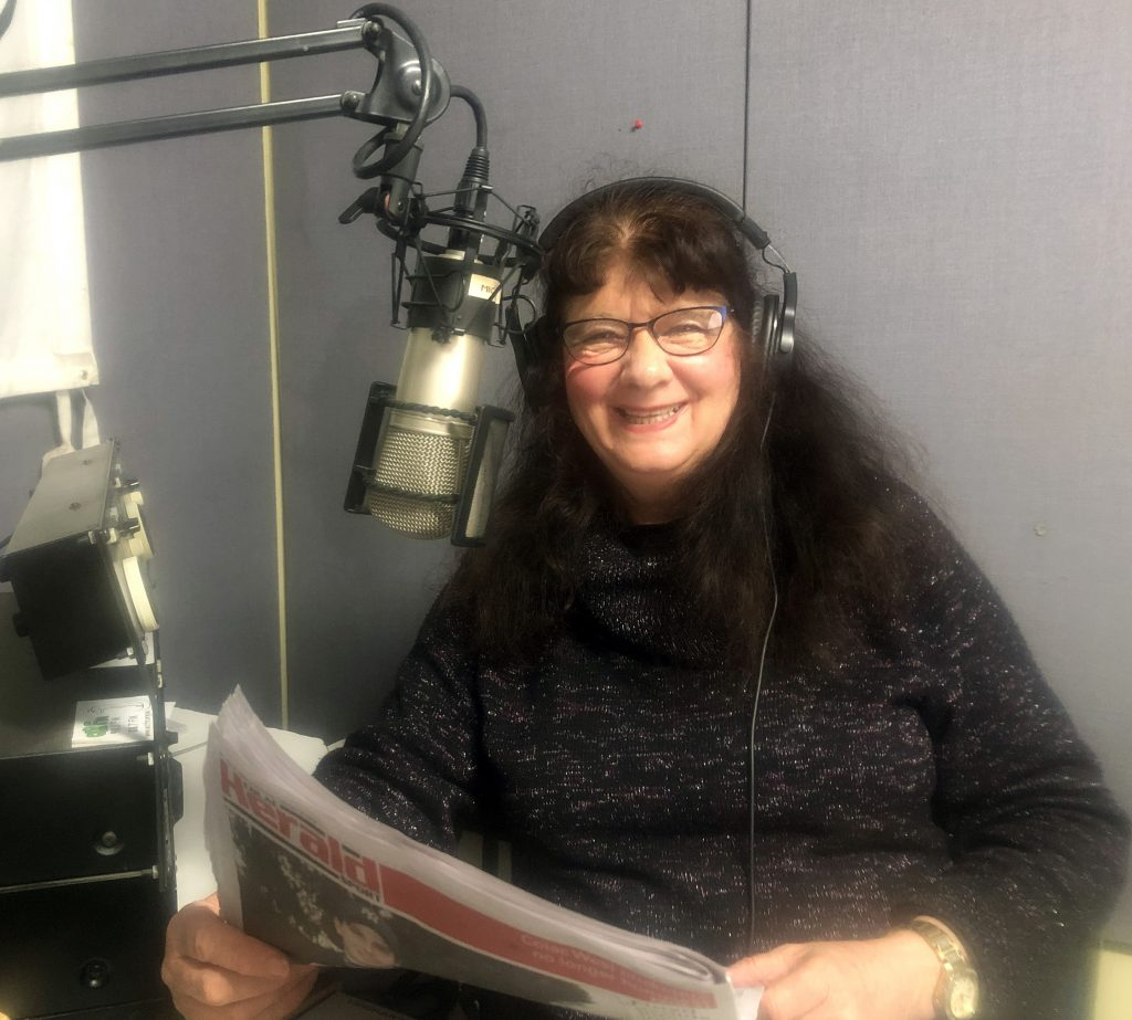 Older woman wearing glasses and holding a newspaper, smiles for the camera in the OCR-FM studio.